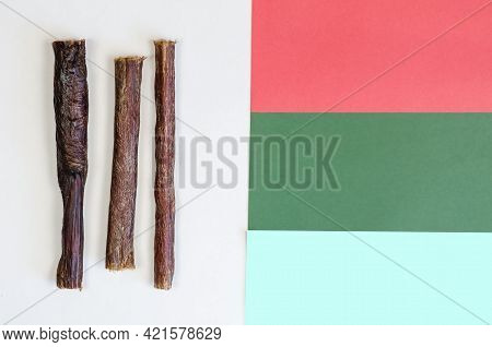 Dehydrated Dog Treat Sticks Randomly On A Colorful Background. Three Chewy Goodies. Dried Beef Esoph