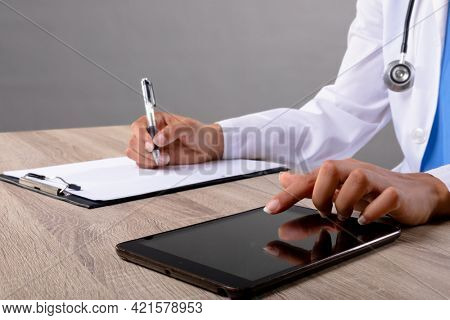 Mid section of female doctor taking notes and using digital tablet against grey background. healthcare and medical professionalism concept