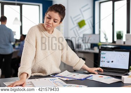 Financial Charts Analysed In Start Up Company By Business Owner Standing At Desk. Successful Corpora