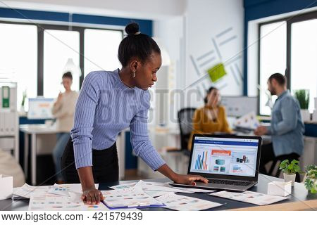 Concentrated African Black Businesswoman Scroling Through Statistics On Laptop Standing Up. Diverse