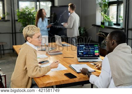 Two economists discussing financial data at meeting in office