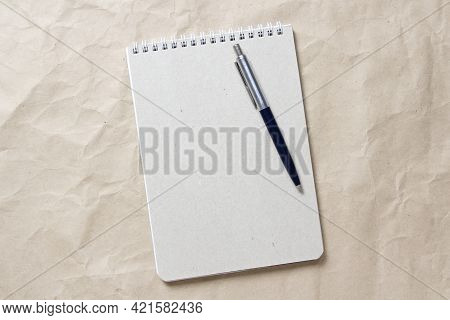 Gray Notepad With White Coiled Spring And Pen On A Background Of Beige Crumpled Craft Paper. With Em