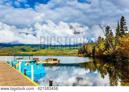 Pyramid Lake. Cold sunny day in the Rocky Mountains of Canada. The smooth, cold water reflects the sky and lush cumulus clouds. Boat pier for tourist and fishing boats