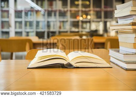 Old Textbook Are Open And Stack Book Placed On A Wooden Table On Blurred Bookshelf In Library Room B
