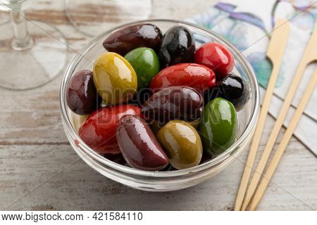 Glass bowl with a variation of different olives close up for a snack