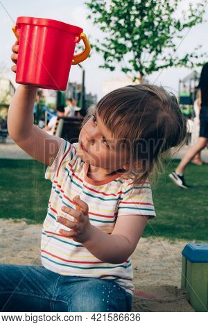 A Cute Little Girl Is Playing In The Sandbox On The Playground. The Child Carefully Watches As The S