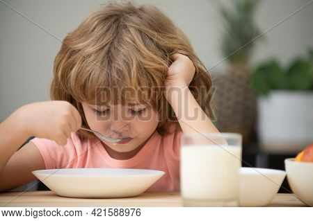 Child Eating Healthy Food At Home. Unhappy Child Have No Appetite. Upset Little Kid Refuse To Eat Or