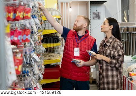 Male shop assistant consulting woman and helping her choose new socket in hardware store