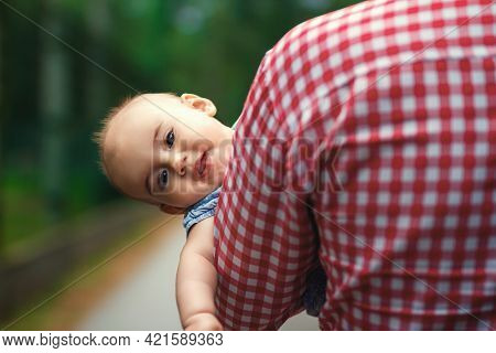 A Father Carries His Little Daughter In His Arms. The Child Peeks Out From Behind Dad\'s Broad Shoul