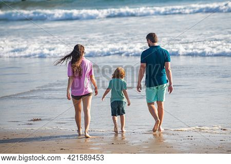 Back View Of Family On The Beach. People Having Fun On Summer Vacation. Father, Mother And Child Hol