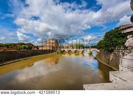 View Of River Tiber With The Holy Angel Castle And Bridge Under A Cloudy Sky In Rome, From The Nearb