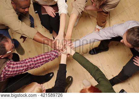 Large group of intercultural people making pile of hands over wooden floor