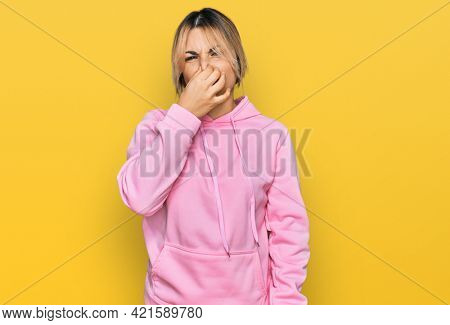 Young caucasian woman wearing casual sweatshirt smelling something stinky and disgusting, intolerable smell, holding breath with fingers on nose. bad smell