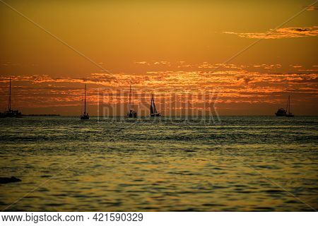 Boat On The Sea At Sunset. Sailboats With Sails. Ocean Yacht Sailing In Ocean Water.