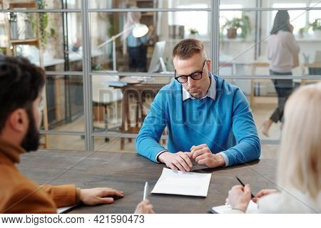 Serious handsome young Caucasian man in eyeglasses sitting at table in front of company representatives and reading contract at job interview