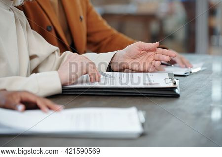 Close-up of unrecognizable recruiters sitting in row and reading CV while asking question to applicant at job interview