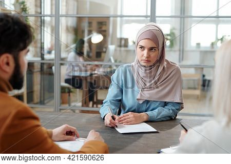 Serious young Arabian woman in hijab sitting at table in front of HR managers and filling questionnaire at job interview