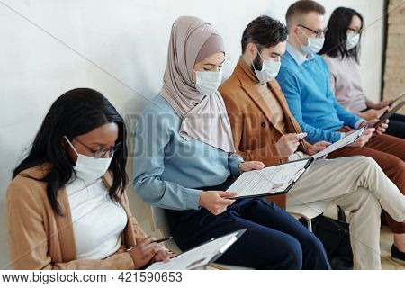 Group of young multi-ethnic job candidates in masks sitting in row and examining resume before interview