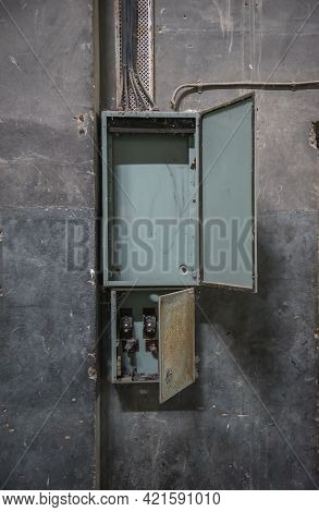 Empty Old Switchboard. Open Distribution Panel Box On Damaged Concrete Wall In Abandoned Building