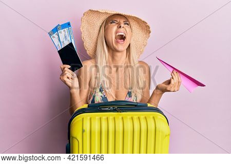 Young blonde woman wearing bikini holding passport and paper plane angry and mad screaming frustrated and furious, shouting with anger looking up.