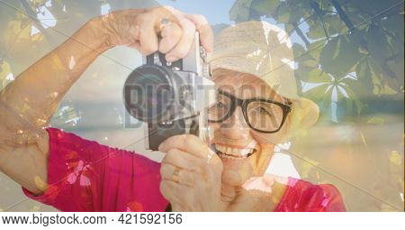 Composition of senior woman taking photo with camera on beach and autumn foliage. healthy active retirement lifestyle concept digitally generated image.