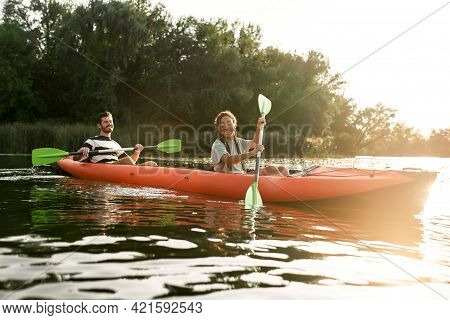 Two Adventurous Young Friends Kayaking In A River Surrounded By The Beautiful Nature On A Summer Day