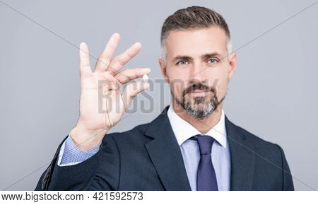 Mature Business Man With Grizzled Hair In Suit Hold Pill In Hand With Ok Gesture, Energy Remedy
