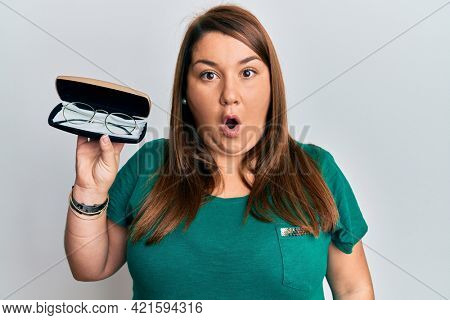 Beautiful brunette plus size woman holding glasses in eyewear case scared and amazed with open mouth for surprise, disbelief face