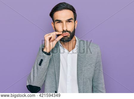 Young hispanic man wearing business clothes mouth and lips shut as zip with fingers. secret and silent, taboo talking