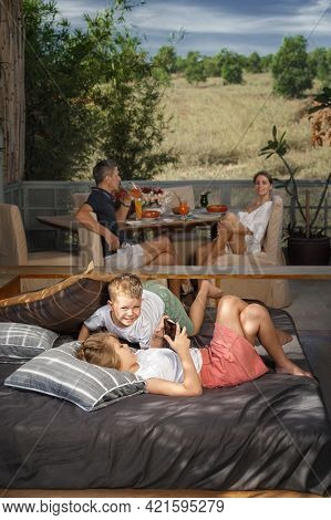 Happy family at home. Sister and brother playing and laughing on the bed, on veranda. European family relaxing on balcony in summer enjoying their vacation.