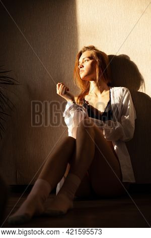 Beautiful Attractive Blonde Girl Is Sitting In Her Room Resting Under The Sunlight.