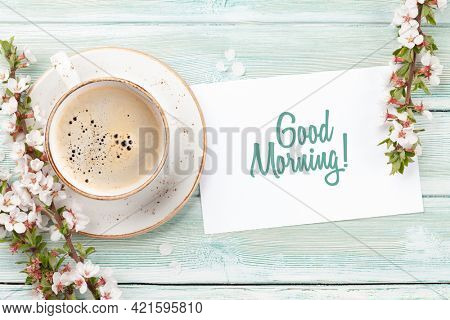 Morning espresso coffee cup on wooden table, greeting card and cherry blossom. Top view flat lay with copy space