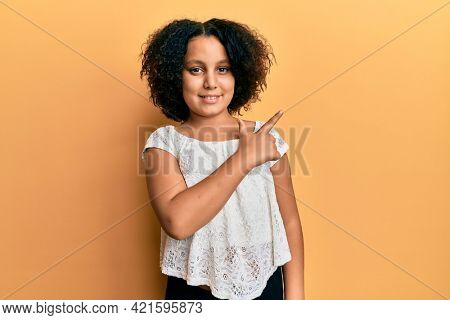 Young little girl with afro hair wearing casual clothes cheerful with a smile of face pointing with hand and finger up to the side with happy and natural expression on face