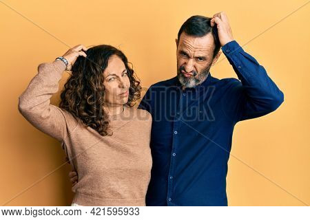 Middle age hispanic couple wearing casual clothes confuse and wondering about question. uncertain with doubt, thinking with hand on head. pensive concept.