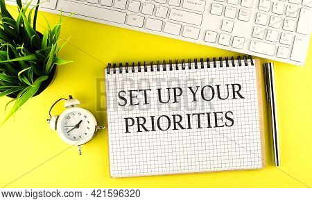Set Up Your Priorities Text On Notebook With Keyboard , Pen And Alarm Clock On Yellow Background