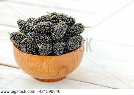 Fresh Black Mulberry In A Wooden Bowl On The White Wooden Table. Mulberry Close-up. Organik Freshly