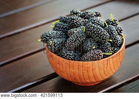 Fresh Black Mulberry In A Wooden Bowl On The Wooden Table. Mulberry Close-up. Organik Freshly Harves