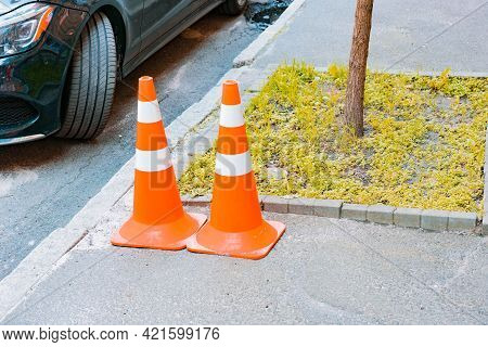 Two Orange Traffic Cones With White Stripes Stands On A Sidewalk Near Tree And Ground. Security. Pav