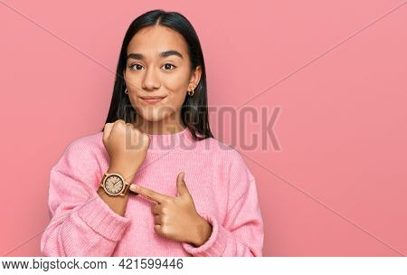 Young asian woman wearing casual winter sweater in hurry pointing to watch time, impatience, looking at the camera with relaxed expression