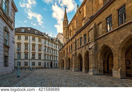 View of famous Minoritenkirche and old cobblestone street in old city of Vienna, Austria.
