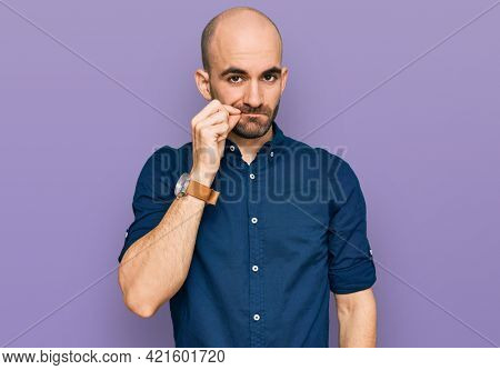 Young hispanic man wearing casual clothes mouth and lips shut as zip with fingers. secret and silent, taboo talking