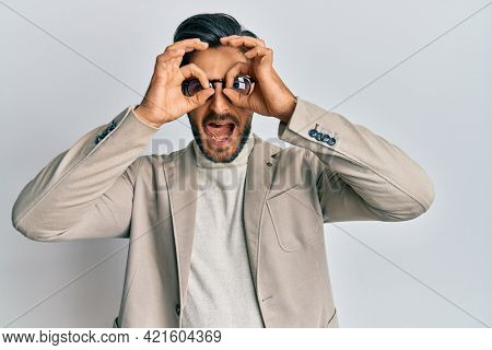 Young hispanic man wearing business jacket and glasses doing ok gesture like binoculars sticking tongue out, eyes looking through fingers. crazy expression.