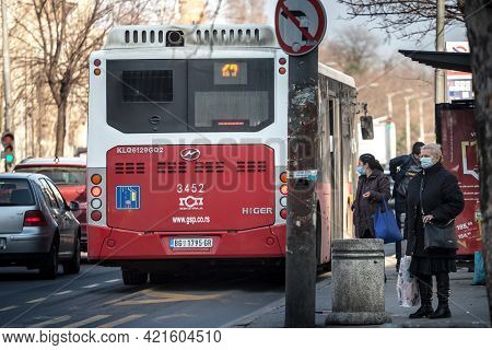 Belgrade, Serbia - March 13, 2021: Senior Old Woman Waiting At A Bus Stop For Public Transportation