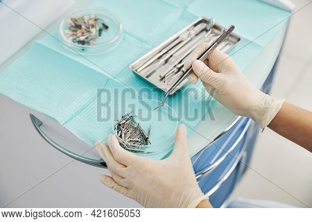 Dental Burs Lying In Glass Bowl While Dentist Taking One