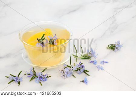 Rosemary herb and lemon herbal tea for immune boost high in antioxidants and vitamin c  in a glass cup on marble.