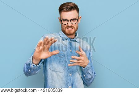 Young redhead man wearing casual denim shirt disgusted expression, displeased and fearful doing disgust face because aversion reaction. with hands raised