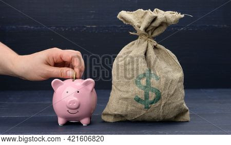 A Full Sack With An American Dollar Sign And A Pink Ceramic Piggy Bank, A Hand Tosses A Coin. The Co