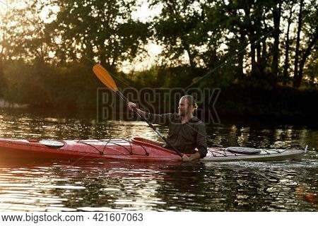 Concentrated Young Caucasian Man Paddling Kayak On A Lake Surrounded By Nature On A Summer Afternoon
