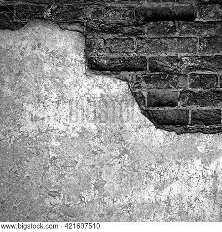 Dark Black Grunge Brick Wall With Peeling Stucco Crack. Damaged Surface Of Aged Block Loft Backgroun