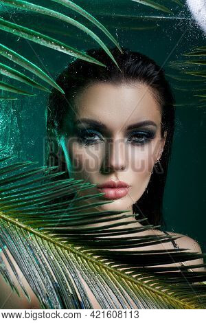 Beauty Woman In Palm Leaves Wet Makeup, Tropical Portrait Girl In Green Swimsuit In Branches Palm Tr